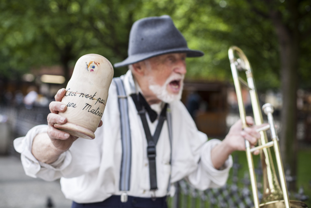 An eccentric Czech jazz musician dancing in the vicinity of the Old Town Square next to one of the pinhole Matrioskas.